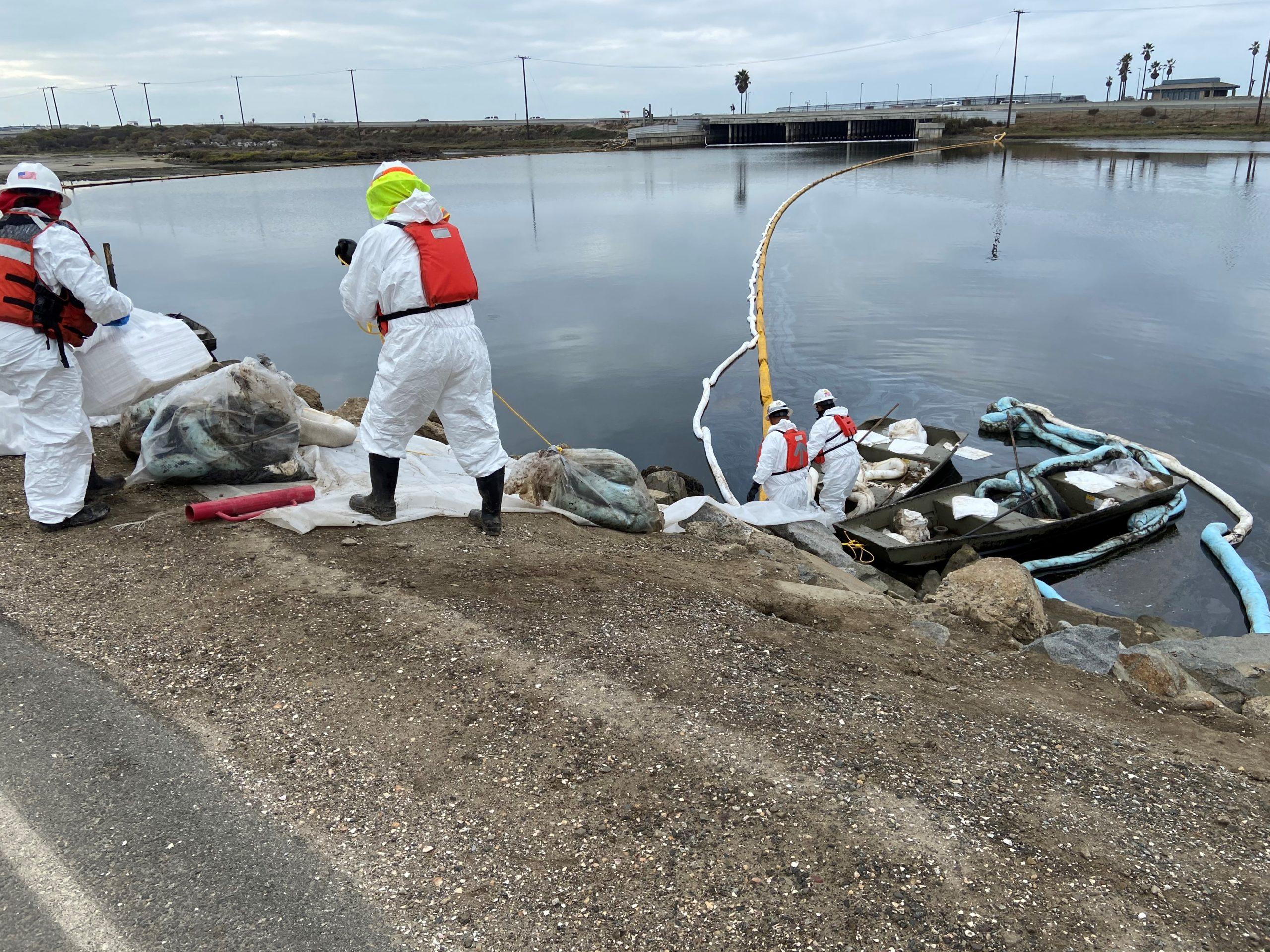 Contractors remove oil near a marsh area in Huntington Beach, California