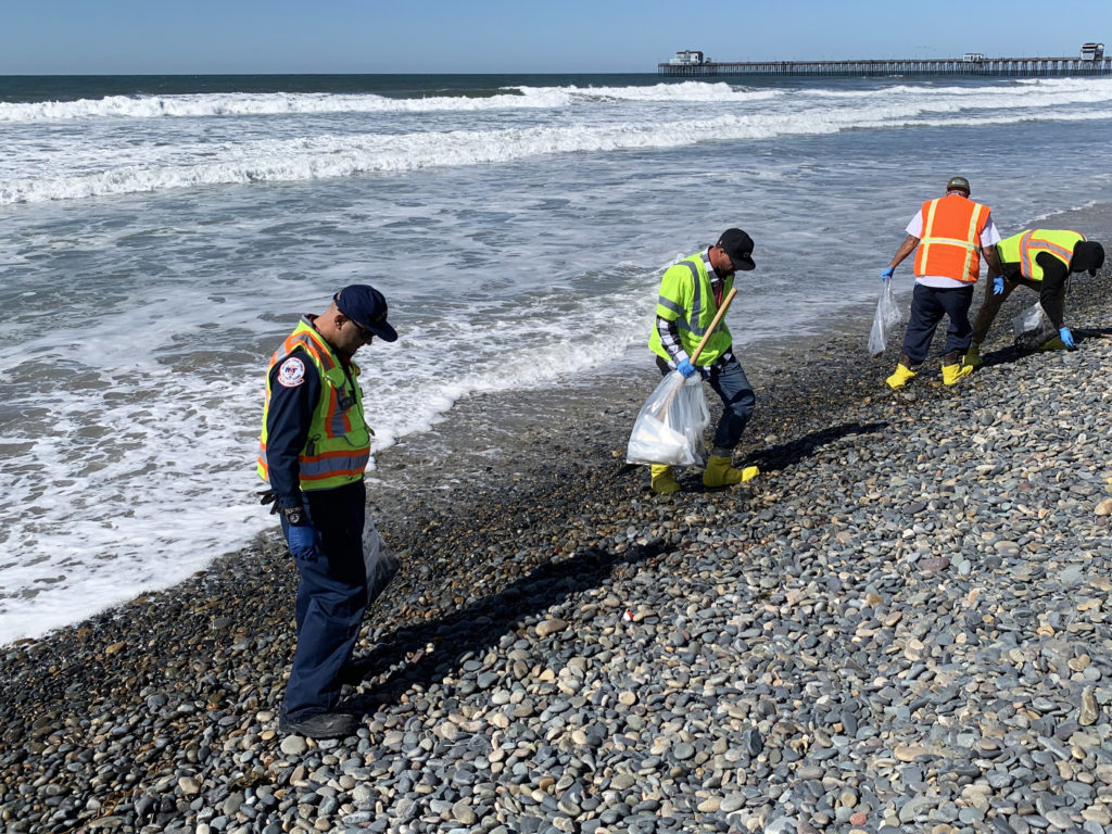 Contractors on a hotshot team to remove tar balls from shores in Oceanside Harbor Beach in San Diego County