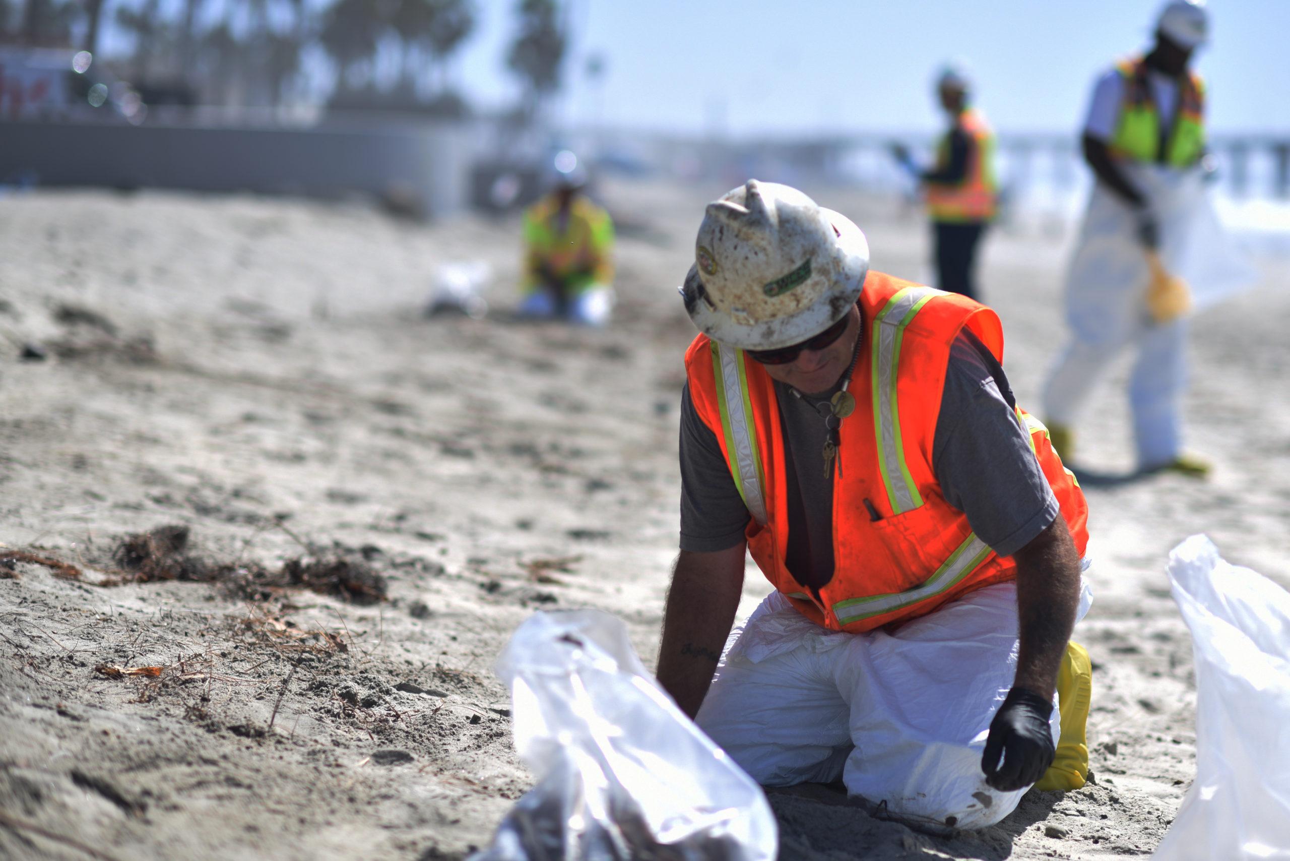 A clean up team member removes tar balls from Oceanside Harbor