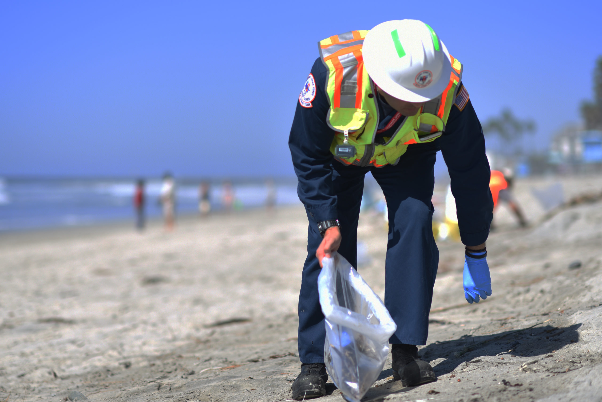 Petty Officer 1st Class Christopher Romero and contracted cleanup teams remove tar balls from the shoreline in Oceanside Harbor