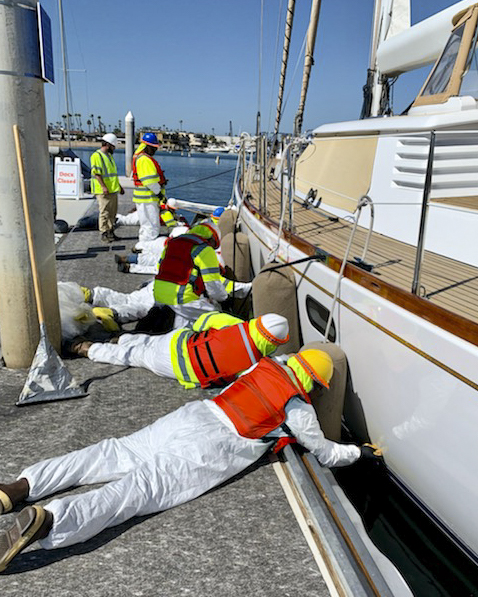 Men clean the hull of a sailboat