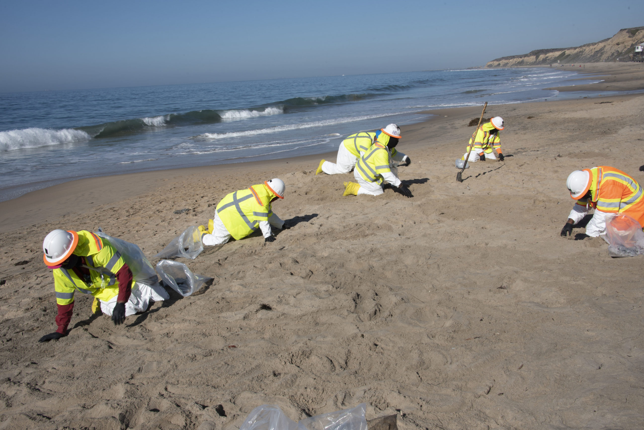 Contractors clean oil from the beach